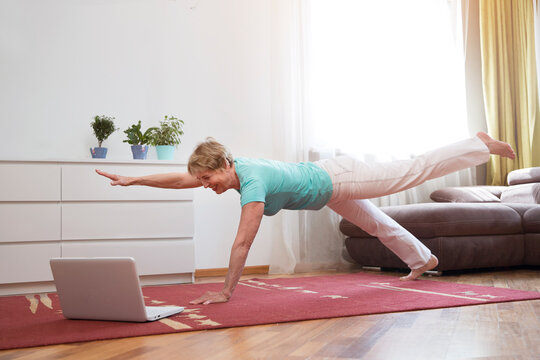 active senior woman doing yoga fitness exercise and watching online workout tutorials on the laptop in living room at home.  home fitness, activewear. Healthy and sport lifestyle.