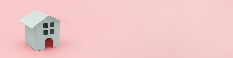 Simply minimal design with miniature white toy house isolated on pink pastel colourful background. Mortgage property insurance dream home concept. Flat lay top view copy space, banner