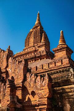 Ancient pagoda exterior in Bagan archaeological zone, Myanmar (Burma) against deep blue sky.