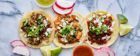 Wall Mural - row of assorted mexican street tacos with garnishes in wide banner composition