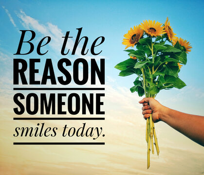 Inspirational quote - Be the reason someone smiles today. With a hand holding a bunch of sunflowers against bright blue sky background. Motivational text message with flowers and sky background.