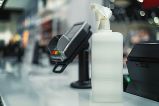 Sanitizer bottle in shop for customers near contactless payment terminal, close up.