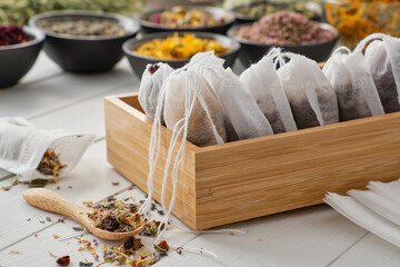 Wooden box of tea bags filled with dry medicinal herbs and flowers. Bowls of medicinal plants on...