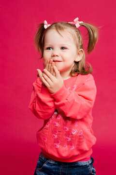 Positive smiling little girl with blue eyes, in pink sweatshirt with mickey mouse and jeans, with two tails hairstyle. Sweet funny child having fun, hiding surprised face by hands. Pink background.