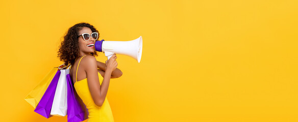 Happy beautiful woman with shopping bags and megaphone on isolated colorful yellow banner background for sale and discount concepts