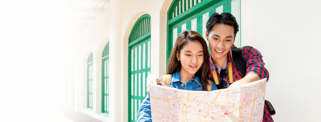Panoramic banner image of Asian couple looking at the map while traveling on vacation in old city area of Bangkok Thailand