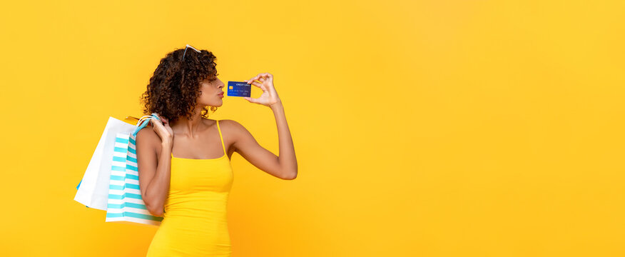Fashionable curly hair woman carrying shopping bags holding credit card on yellow banner background with copy space