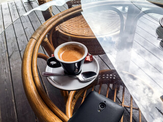 coffee cup on a glass table with sky reflections. coffee terrace with tables and chairs. street cafe