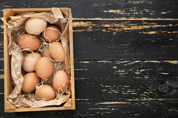 Box with chicken eggs on wooden background