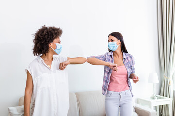 Elbow bump. New novel greeting to avoid the spread of coronavirus. Two women friends meet with bare hands. Instead of greeting with a hug or handshake, they bump elbows instead.