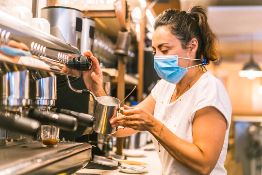 A waitress with a face mask in a bar. New normality, security measures after the coronavirus pandemic, social distance, covid-19. Preparing a coffee