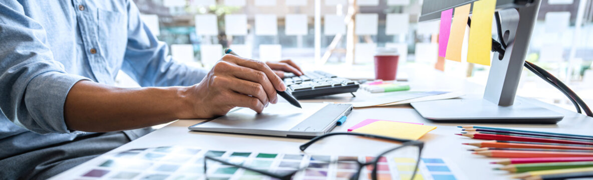 Image of male creative graphic designer working on color selection and drawing on graphics tablet at workplace with work tools and accessories in workspace