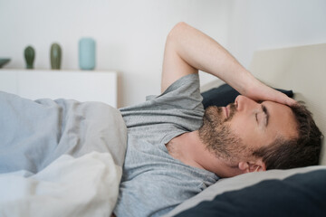 Restless man waking up early with headache after rough night