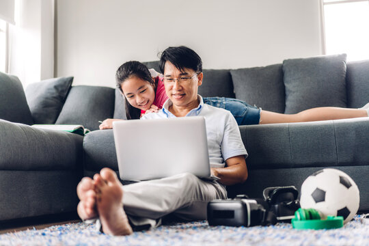 Smiling asian man relaxing using laptop computer working and video conference meeting chat with his girl daughter learning reading book and studying knowledge at home.work from home concept