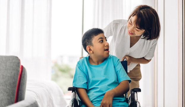 Portrait of enjoy happy love family asian mother playing and carer helping look at disabled son child sitting in wheelchair moments good time at home.disability care concept