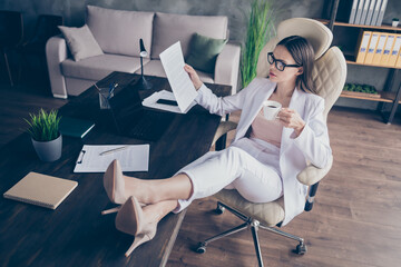 Photo of attractive business lady legs high-heels on desktop table remote work resting drink hot...
