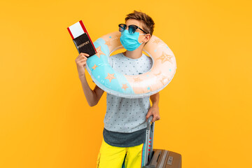 a teenage tourist in a protective medical mask stands with a passport and suitcase, as well as an...