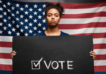 Black woman holding Vote sign against american flag