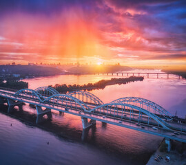 Autocollants de meubles Corail Aerial view of beautiful bridge at sunset in Kiev, Ukraine. Landscape with bridge, river, city, colorful sky with red clouds in summer. Cityscape with road, buildings, reflection in water. Top view