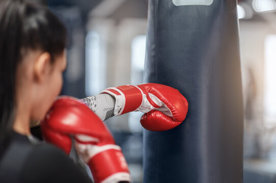 Female boxer in gloves hitting big punching ball during self defence class at gym, empty space