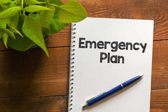 EMERGENCY PLAN text written in an office notebook on a wooden table.