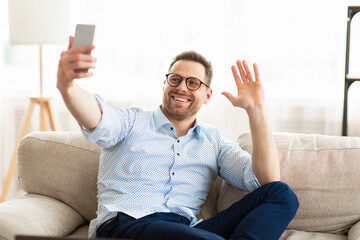 Happy man using mobile phone for video call