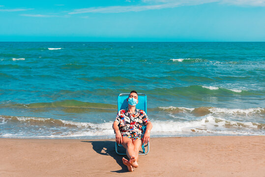man wearing a surgical mask on the beach