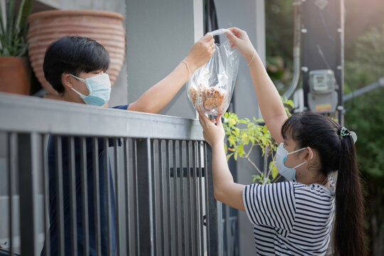 Young lady deliver a snack and goods to her neighbor. Both of them wearing a facemask to prevent themselve from COVID-19.
