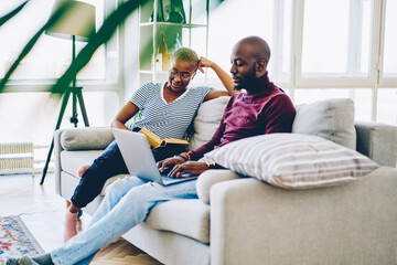 Positive dark skinned marriage spending free time at home interior, african american woman reading...