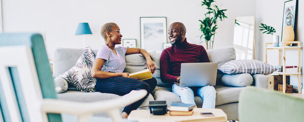Cheerful african american marriage spending time at home enjoying free time together, positive woman sitting with book while communicating with her husband using laptop computer and wifi in apartment.