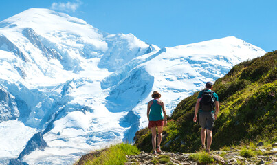 Fototapeten Blau Couple of hikers walking toward beautiful snow covered Mont Blanc mountain in French Alps in summer. France active tourism background. Travel in nature concept.