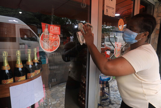 A woman wearing a face mask cleans a wine shop window ,amid the outbreak of the coronavirus disease (COVID-19), in Adjame a neighbourhood of Abidjan