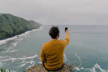 Rear view of man sitting on a rock at the coast taking a smartphone picture on Sao Miguel Island, Azores, Portugal