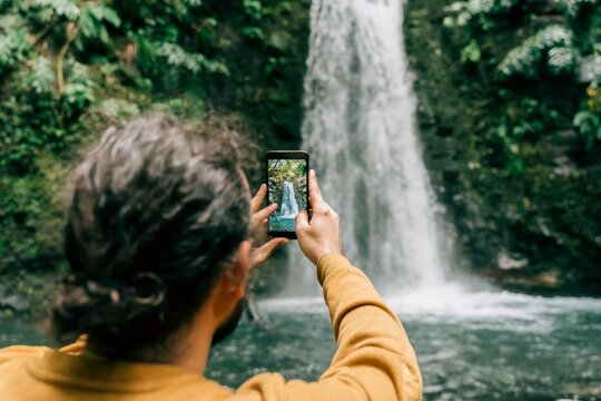 Rear view of man taking smartphone picture at a waterfall on Sao Miguel Island, Azores, Portugal