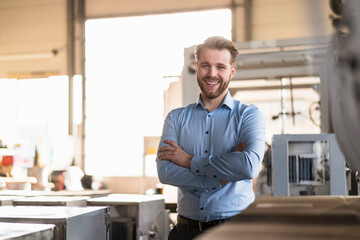 Portrait of a happy young businessman in a factory