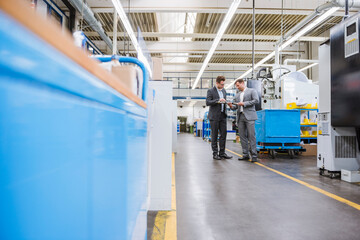Two businessmen examining a product in a factory