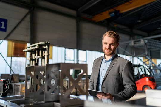 Portrait of a smiling young businessman with tablet in a factory