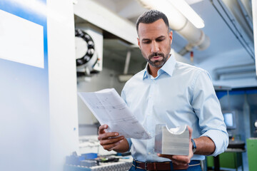 Businessman holding plan and workpiece in factory hall