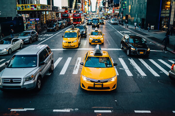Yellow cabs moving on road of Manhattan passing buildings and commercial on street during daytime, busy traffic on avenues in New York downtown with cars and cab taxis stopping near crossroad in city