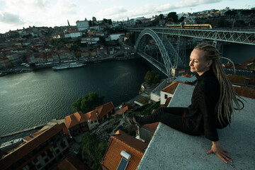 Tourist woman sitting in front of Douro river and Dom luis I bridge in the gloomy weather, Porto, Portugal.