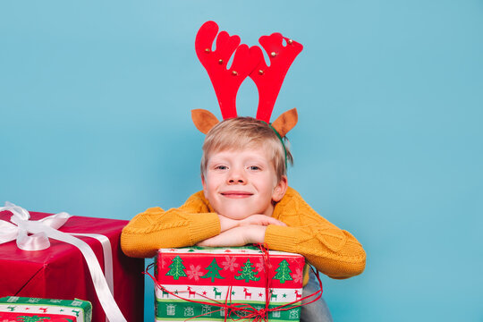 Smiling child boy in Chistmas reindeer antlers holding a pile of gift boxes on blue background