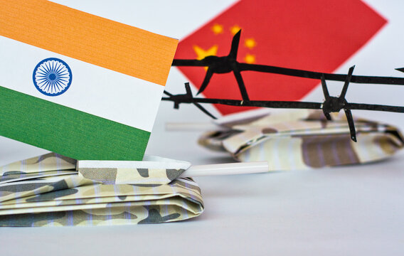Chinese and Indian flags on tanks between barbed wire, grunge style photo