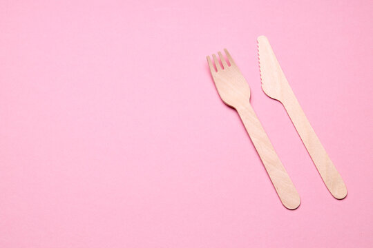 eco-friendly disposable utensills concept. close up bamboo or wooden cutlery over pink color background.