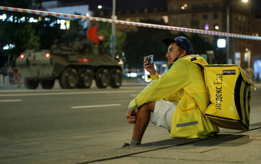 A Yandex Food courier takes pictures of military vehicles during a rehearsal for the Victory Day parade in Moscow