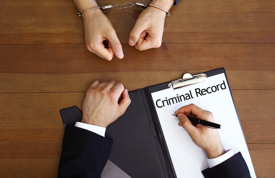 Police officer examining criminal record at desk, top view