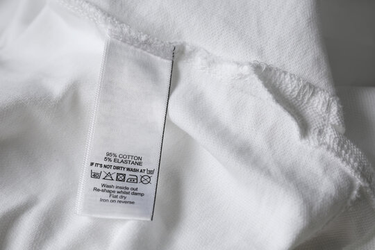 Clothing label with care symbols and material content on white shirt, closeup view