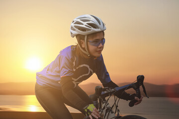 Beautiful asian girl cyclist riding a bike on the road towards the sunset. Hobbies and sports