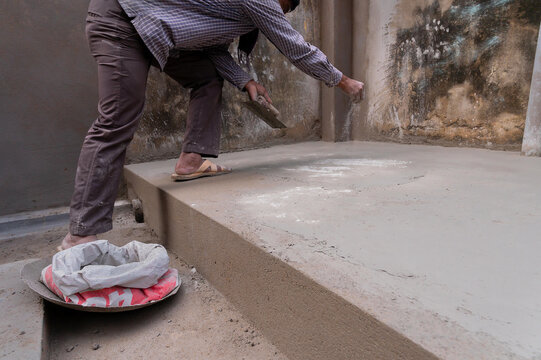 Indian labour levelliing plastered floor using flat trowel and distributing cement manually by hand, Stock image.