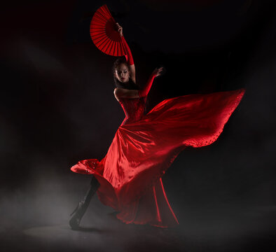 Flamenco woman spanish dancer in red dres performs with fan in dance at black background, studio shot