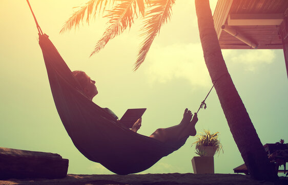 Woman an using a digital tablet  while relaxing in a hammock on a sand tropical summer beach